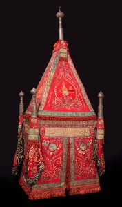 Sitr (or sitarah) for the mahmal, bearing the tughra of Sultan Abdülaziz, presented by Isma'il Pasha, the khedive of Egypt Ottoman Egypt, Cairo, 1867-76; red silk with green silk appliqués, embroidered in silver and silver-gilt wire over cotton and silk thread padding; with contemporary banners and copper-alloy finials, and a wooden frame, probably contemporary 400 (approx. height assembled) x 130 x 102 cm