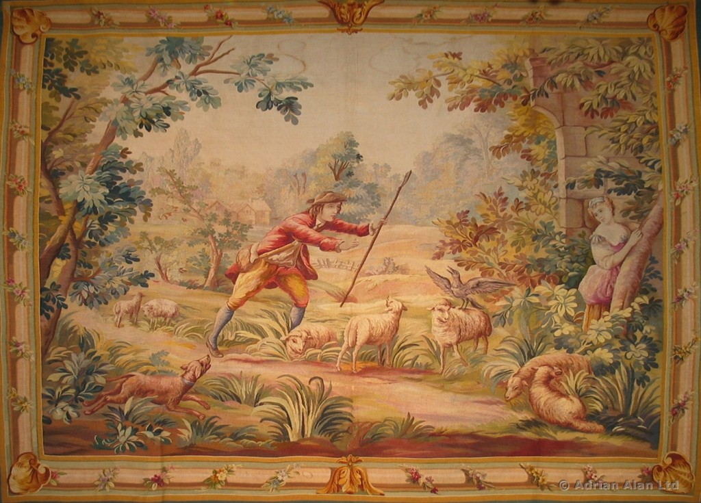 A FINE AUBUSSON PASTORAL TAPESTRY DEPICTING A SHEPHERD AND SHEPHERDESS IN A PICTURESQUE LANDSCAPE C. 1900, FRANCE