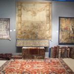 Aaron Nejad, London, stand showing a 19th century French tapestry fragment above a fine all-over design Heriz on stand