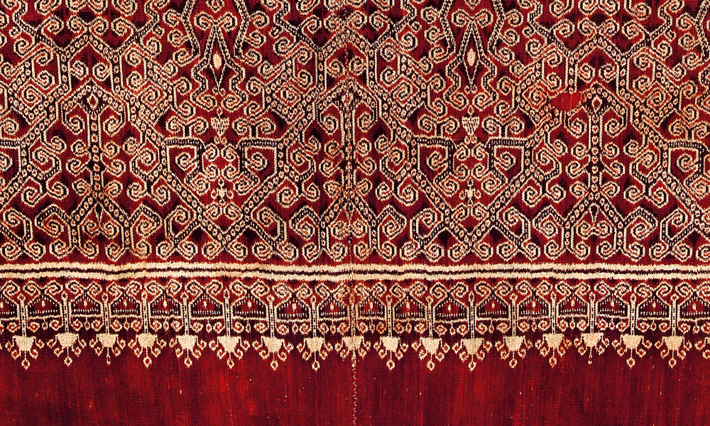 GUJARAT  Mashru textile (detail), western India, late 19th century. Silk, warp-ikat stripes alternating with brocaded stripes on cotton wefts. Sarabhai Foundation - Calico Museum of Textiles, Ahmedabad, 872. Woven in silk and cotton, this vertically striped fabric is known as mashru, literally 'that which is in accordance with Sharia', the Muslim holy law which disapproves of garments such as pajama made of silk only. While outwardly opulent, only the more conservative cotton side of the mashru would touch the skin of the devout. Alternating with the red warp-ikat bands with white chevrons are patterned bands in a brocading technique, which contrasts the dark silk warps with the visible white cotton wefts.