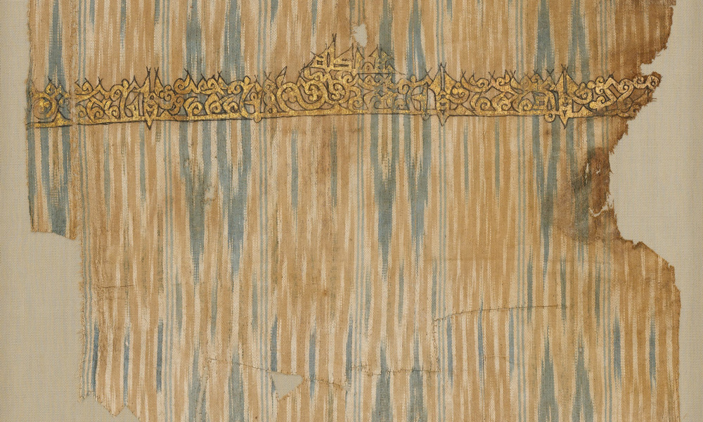 YEMEN Tiraz fragment (detail), Sana'a, Yemen, Zaydi Imam period, ca. 960–980 ce. Cotton, warpikat with painted inscription in gold leaf. The Cleveland Museum of Art, Purchase from the J. H. Wade Fund, 1950.353. Among the oldest of all ikattechnique textiles are Yemeni cotton warp-ikat tiraz with patterns in variegated shades of indigo blue, tan and ivory and embellished with painted or embroidered pious inscriptions, which were made in workshops in the capital, Sana'a, during the late 9th and 10th centuries. Most surviving pieces of Yemeni ikat were recovered from the ancient middens at Fostat in Egypt. The warpikat technique is called 'a sb in Arabic.