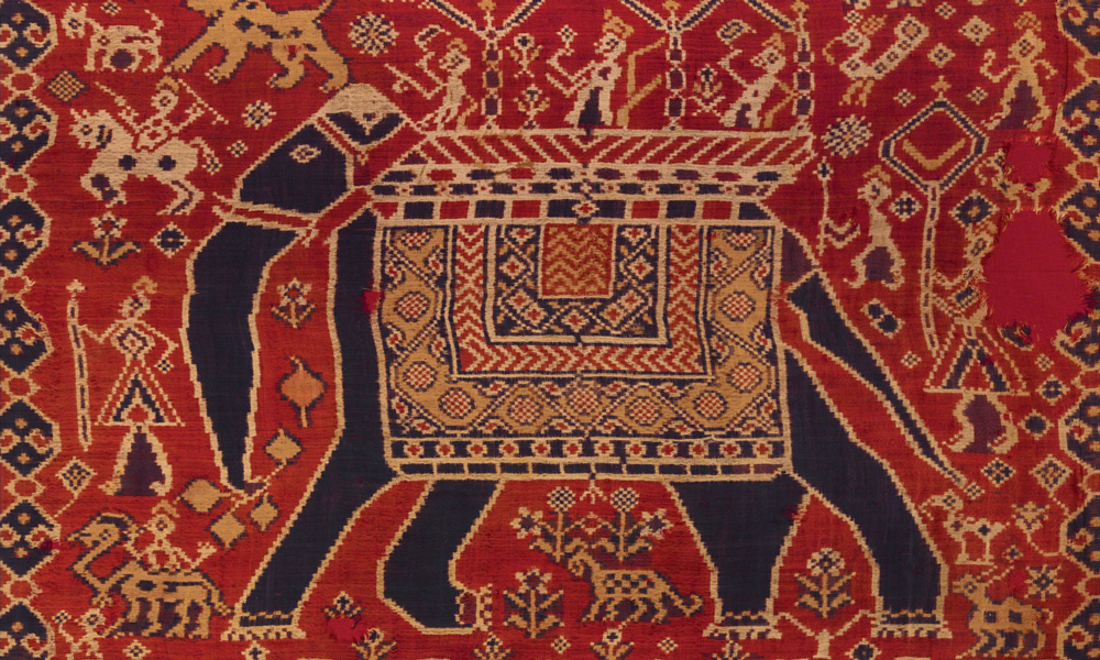 GUJARAT  Elephant patola ceremonial cloth (detail), western India, 18th century. Silk, warp- and weft-ikat. Heidi and Helmut Neumann Collection, Switzerland. There are two primary design types of Gujarati fin e silk double-ikat patola, with the design carried on both warp and weft threads: the majority are patterned with abstracted floral motifs, while those examples decorated with caparisoned elephants, as here, are altogether rarer. The oldest surviving examples are seldom found in India, where they were used as clothing and were worn out, but rather in the islands of Indonesia, where they were imported for use in ceremonies and thus preserved as sacred heirlooms.
