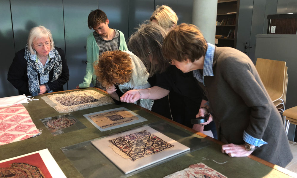 Tour leader Jackie Coulter and Collections Care Manager and Conservator at the Whitworth in Manchester, Ann French show the group Roman Egyptian tunics in the museum stores.