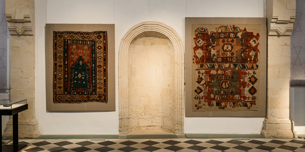 Installation view showing a northeast Anatolian niche kilim from the early 19th century (left) and a Central Anatolian kilim woven before 1800 (right)