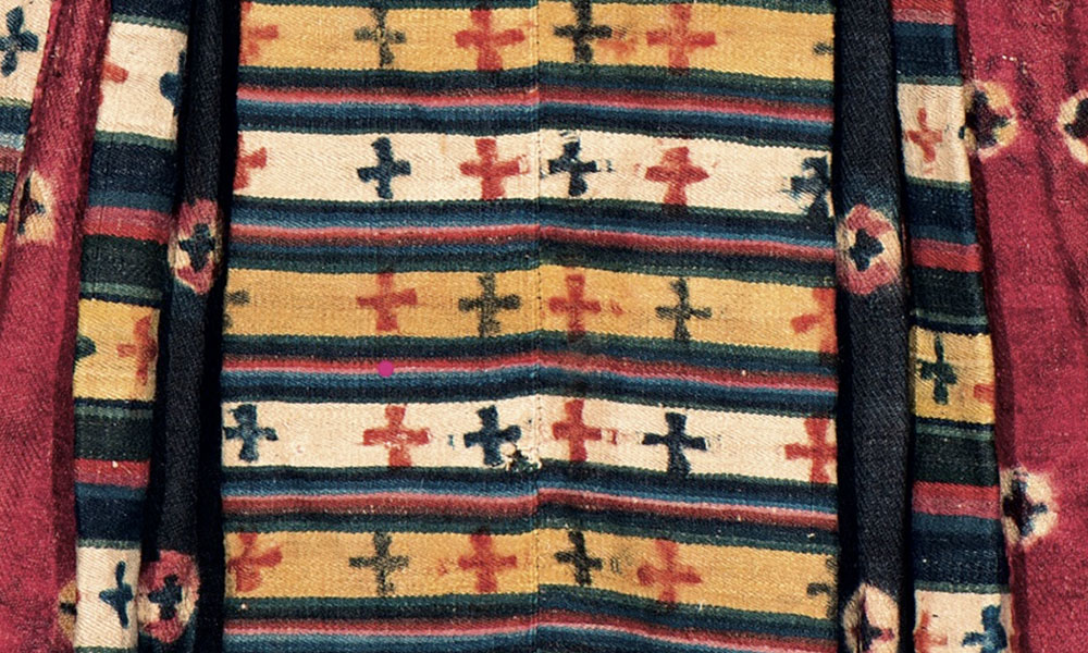 HIMALAYAS  Sul-ma, woman's woollen dress (detail), Ladakh, late 19th/ early 20th century. Bill Liske Collection. Thigma tie-dye designs are found in Tibet and the Indian trans-Himalayan regions of Ladakh, Zanskar, Spiti and Himachal Pradesh. Known as a sul-ma, this style of garment, made from strips of snambu cloth patterned with thigma tie-dyed circles and cruciform motifs, was originally exclusive to the Ladakhi royal family, becoming more generally worn late in the 19th century.