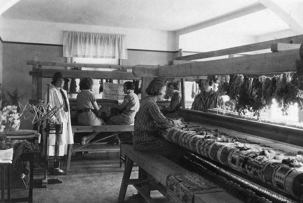 The weaving room at the Båstad workshop, 1929. Märta Måås-Fjetterström wears a hat. The weavers are producing one of two Hästhagen pile rugs for Crown Princess Märtha of Norway