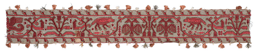 Melos embroidered border fragment, Wace 819. Described by Wace as: 'Emb Long strips—red— gold edged—satin narrow border faced both edges Italian wave pattern with beasts in waves—sirens (2), Eagles (2), Peacocks various types, deer, jugs? &varia. Graecised Italian animals. Alas not ours' Wace Family Collection