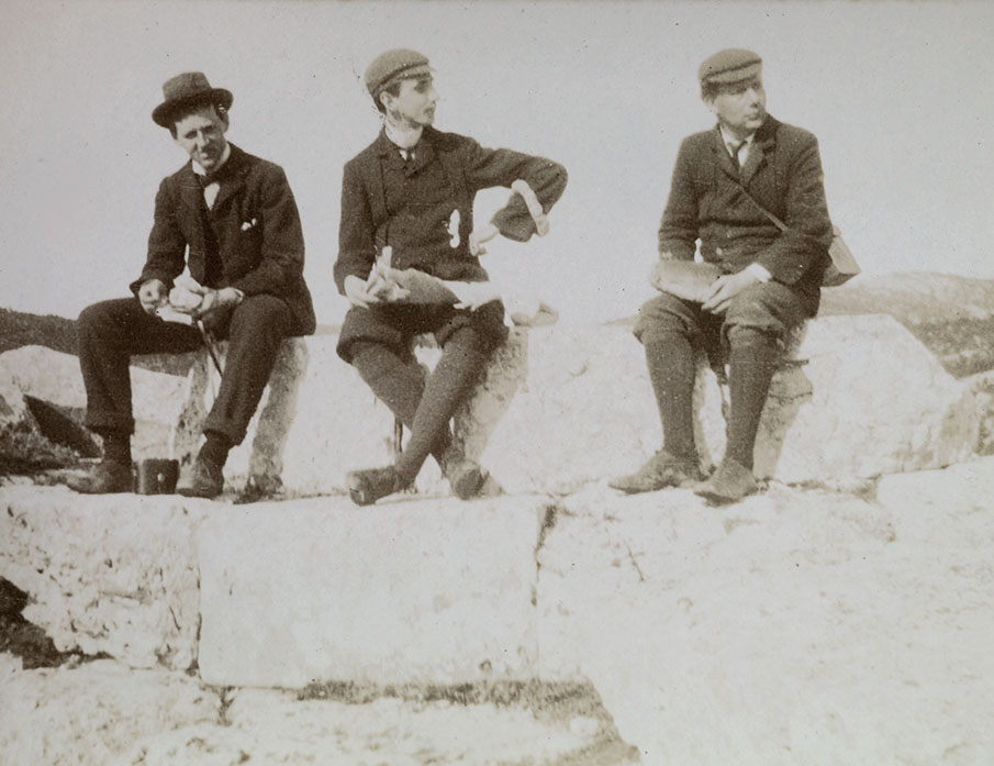 E.W. Webster, A.J.B Wace and R.M. Dawkins, Greece, 1902-03. Annotated on the reverse in Wace's handwriting: 'Left to right E W Webster AJ B Wace R M Dawkins sitting on top of ruined tower at entrance to fort, Phyle. Dawkins holds the bread, I the newspapers & Webster the olives wrapped in paper'. Wace Family Collection