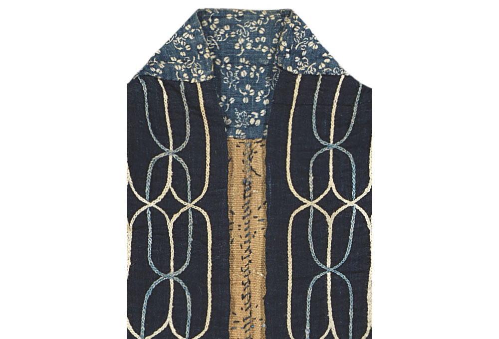 The very top of the collar is made of indigo-dyed Japanese cotton fabric patterned with a small floral design achieved by means of katazome (stencil resist dyeing). In Hokkaido the Ainu were able to trade fish and animal skins for cotton from the Japanese. It was these trade cloths that offered new possibilities for creative expression in Ainu costume