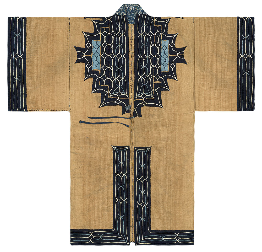 Like many attush intended to be worn for important ceremonies, this robe is decorated with appliqué and embroidery using imported cotton trade cloth and thread. The appliqué is concentrated on the upper back, at the edges of the sleeves and hem, and on either side of the collar. Most of the appliqué is dyed a dark blue with indigo, but there are small segments on the upper back and upper collar that feature a bright, sky-blue shade of indigo that provides a pleasing graphic contrast