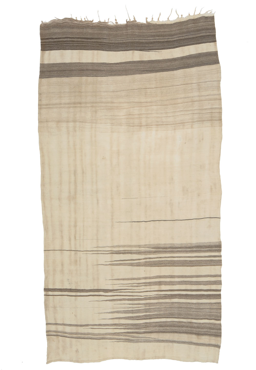 """Berber haik from the Mejjat tribe Anti Atlas, southern Morocco, second half 20th century. 1.10 x 2.20 m (3' 7"""" x 7' 2""""). Alexandra Sachs collection. In this textile the weaver has concentrated on a design that does not rely on colour to create a distinctive strong, graphic quality. The focus is on the undyed wool in various shades and on the simplified pattern repertoire used in everyday garments of the Mejjat region. These aesthetic principles allow for an unadorned design resulting in an almost modern contemporary appearance. The open field, with stripes and peaks running across it, has an effect not unlike the diffuse watercolors of J. M. W. Turner, defining vague outlines of a horizon. An endless range of shades adds depth and vividness to the light background. One can say that the entire composition is a virtuoso play with levels of density. However, the essence of this textile lies in the pure wool, the formal austerity and the rustic 'worn over time' patina. This haik resembles the headscarfs of the Ait Abdellah, with their unmistakable minimalist compositions, of which the best examples feature black peaks in the dark section (HALI 120, p. 79). There could clearly be a connection, since the Ait Abdellah are not situated far away from the Mejjat tribe. Ultimately this haik is one of very few examples representing the zenith of its genre"""