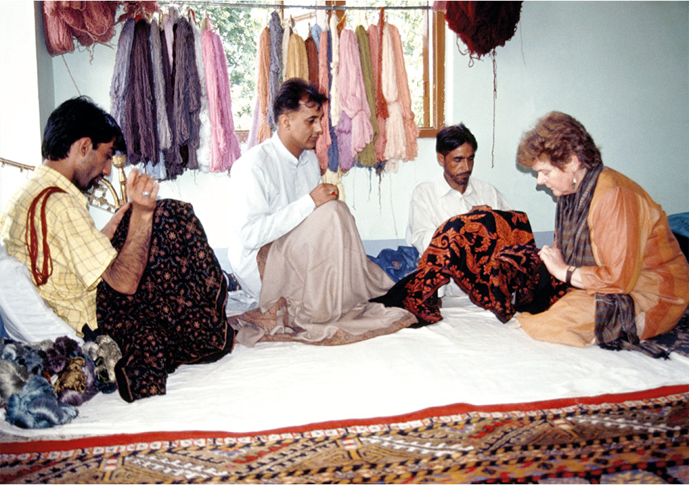 Jenny and Zahid Ali studying a hand-embroidered shawl in a Srinagar workshop