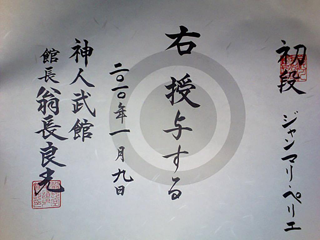<em>La personne mentionnée à droite se voit attribuer le rang indiqué. Donné le 5 janvier 2010.<br> Shinjinbukan. Kanchō, Onaga Yoshimitsu</em><br> <strong>Sho Dan, Jean-marie PERRIER</strong>