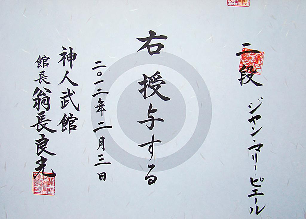 <em>La personne mentionnée à droite se voit attribuer le rang indiqué. Donné le 3 février 2012.<br> Shinjinbukan. Kanchō, Onaga Yoshimitsu</em><br> <strong>Ni Dan, Jean-marie PERRIER</strong>