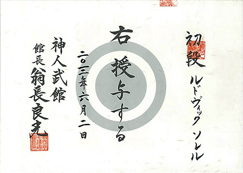 <em>La personne mentionnée à droite se voit attribuer le rang indiqué. Donné le 2 août 2012.<br> Shinjinbukan. Kanchō, Onaga Yoshimitsu</em><br> <strong>Sho Dan, Ludovic SOLER</strong>