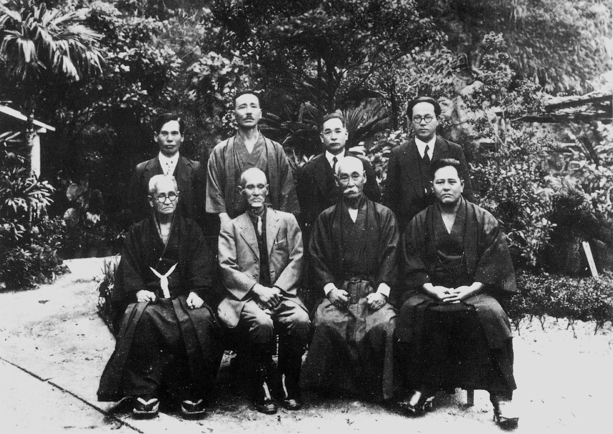 <strong>Au-dessus :</strong> Karate Kenkyukai. Shuri, 1918. <br> <strong>Assis, de droite à gauche :</strong> Miyagi Chōjun, Hanashiro Chōmo, Yabu Kentsu et Chotoku Kyan.<br> <strong>Debout, de droite à gauche : </strong> Nakasone Genwa, Chibana Chōshin, Maeshiro Choryo et Shiroma Shinpan.