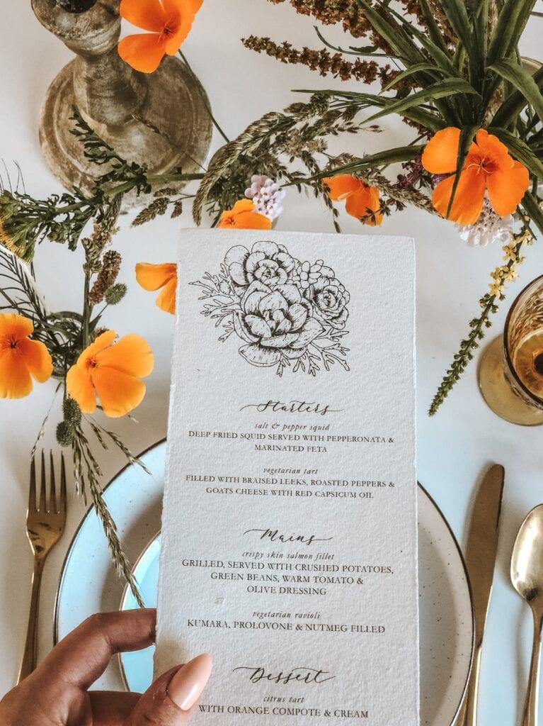 menu infront of orange flowers on wedding tabl