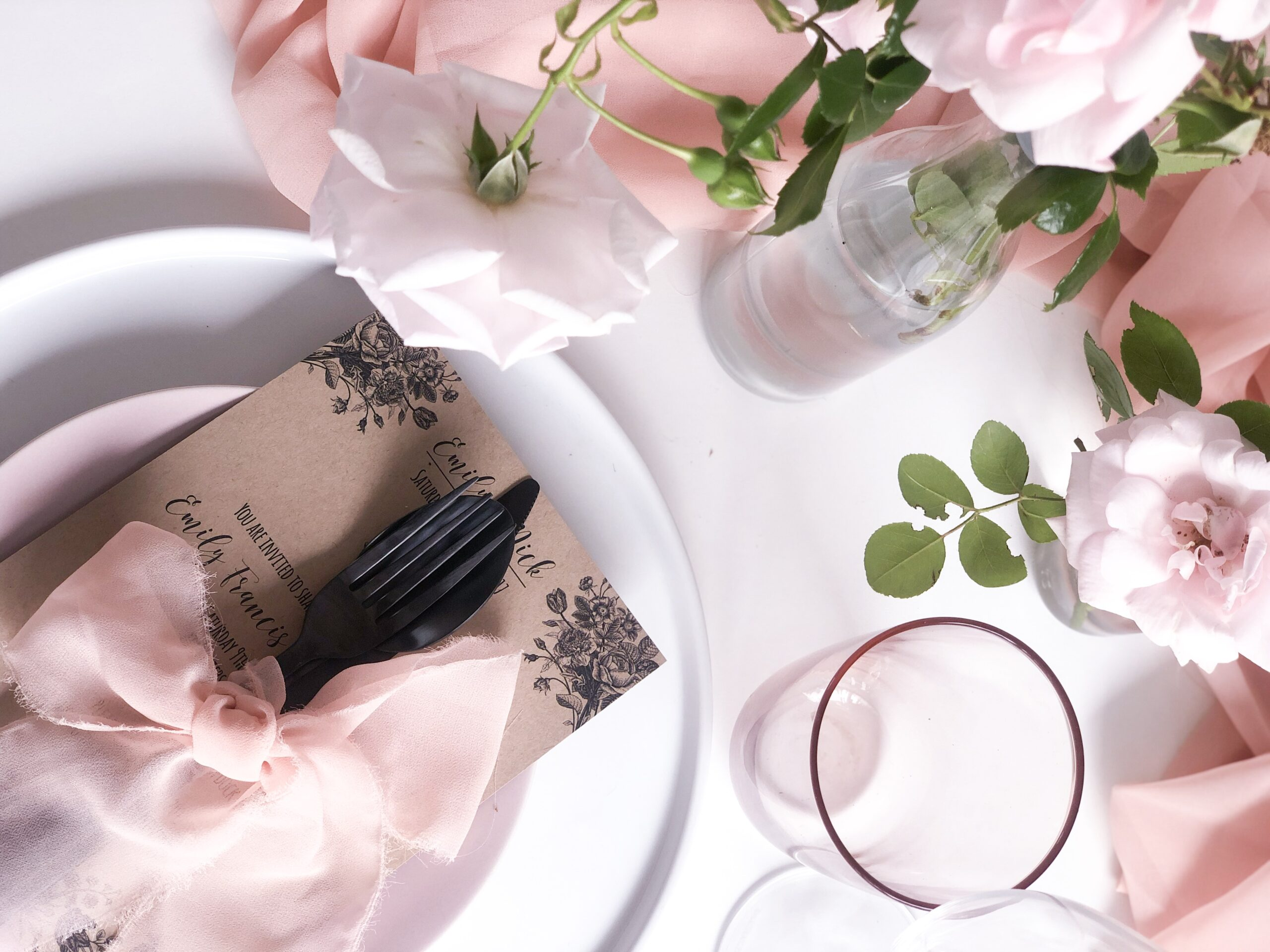 pink bridal table set up with black cutlery and bows