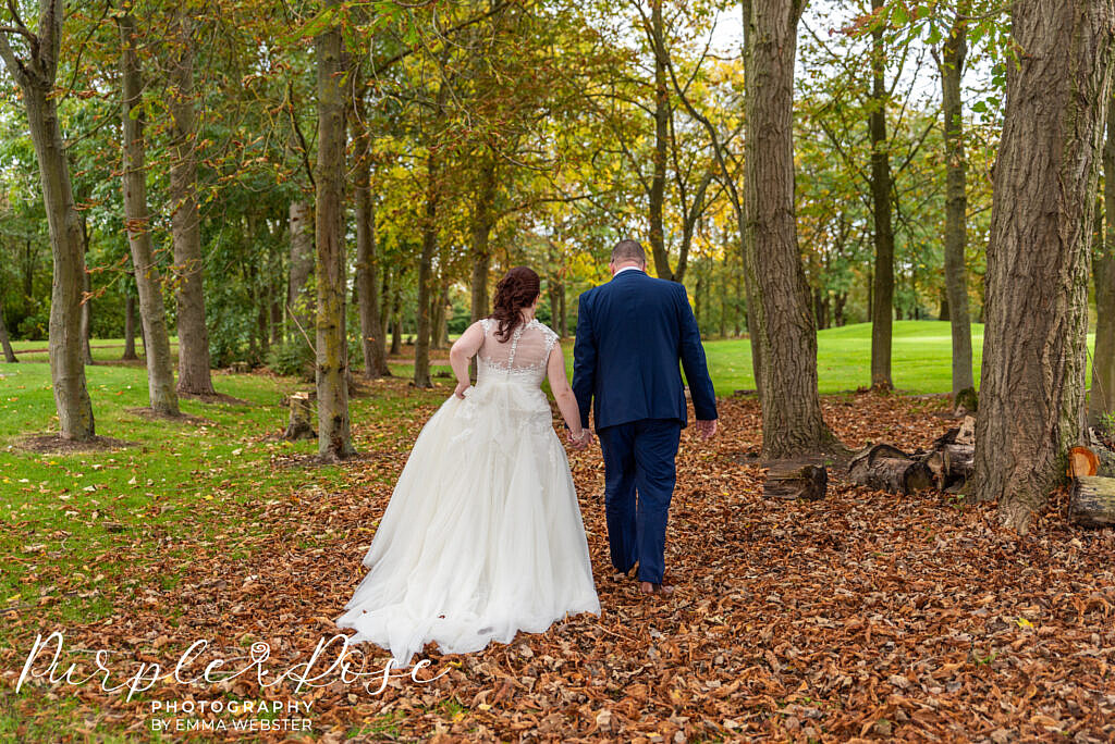 Bride and groom walking through autumn leafs