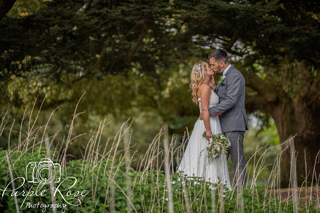 Close up of bride and groom by a pond