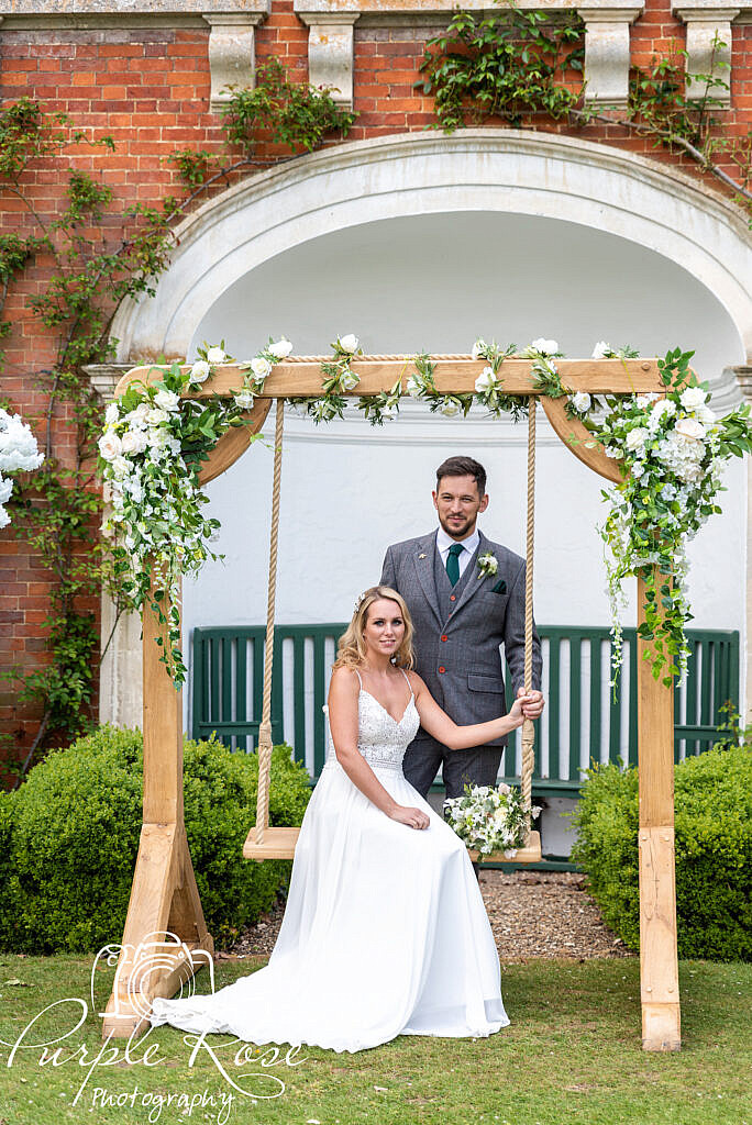 Bride and groom on a swing in their wedding venues garden