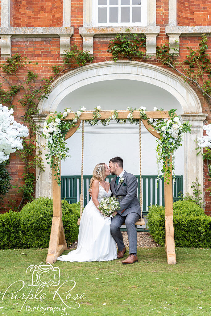 Bride and groom kissing on a swing