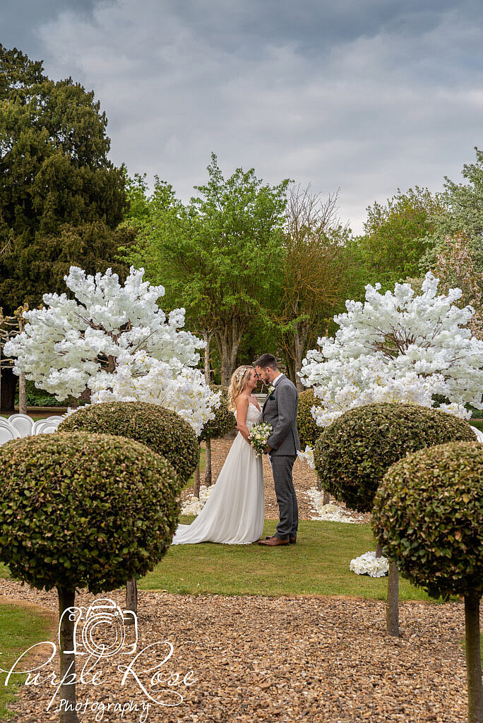 Bride and groom embracing in their venues gardens
