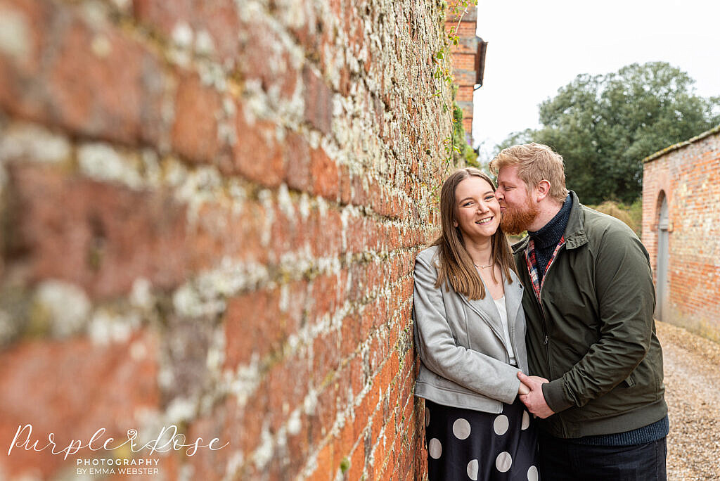 Couple leaning on a brick wall