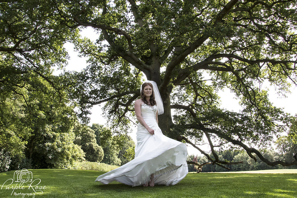 Bride twirling her dress in tree surrounded garden