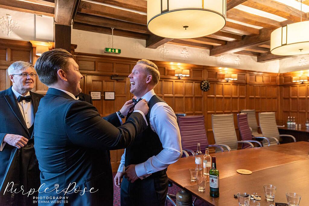 Best man adjusting the grooms bow tie