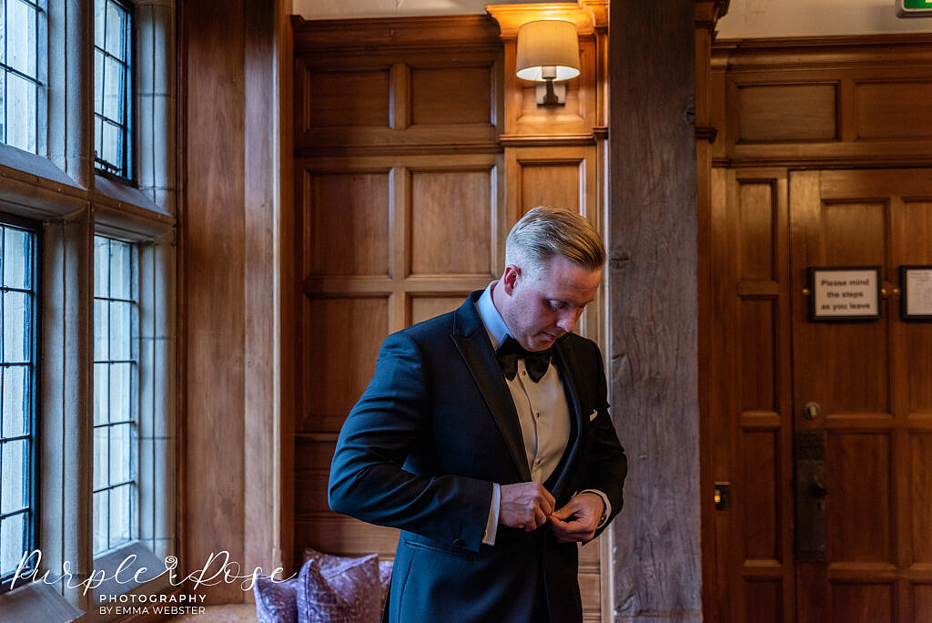 Groom doing up his jacket