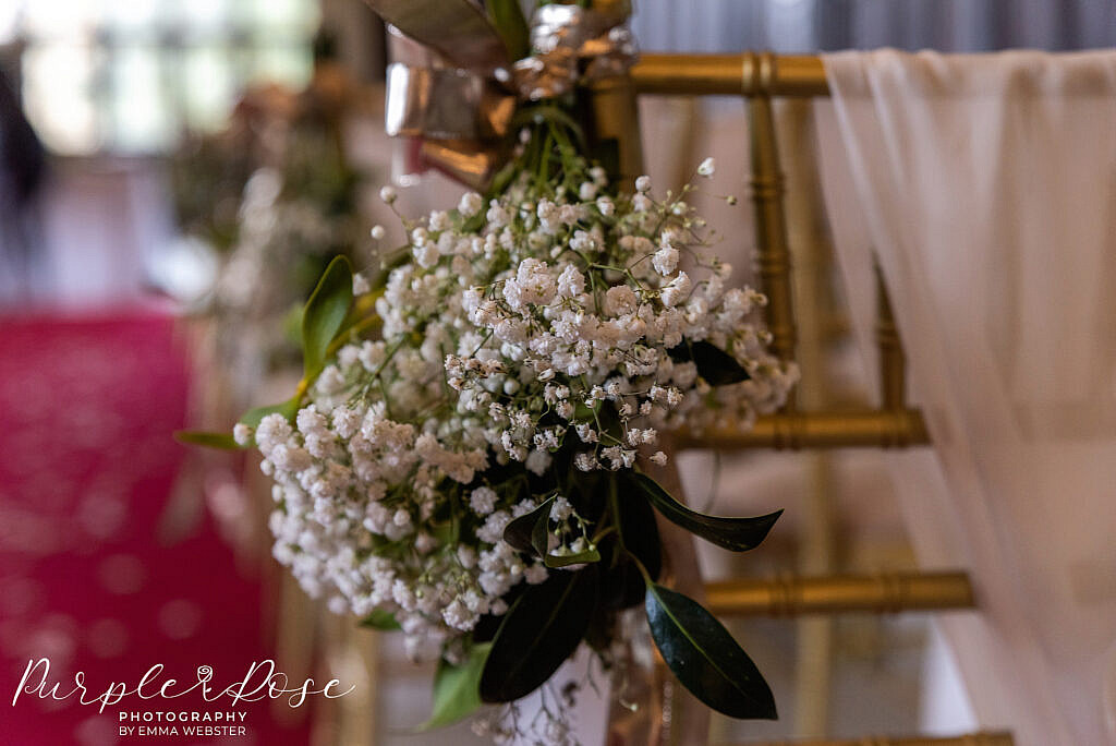 Flowers tied to chair in wedding ceremony room