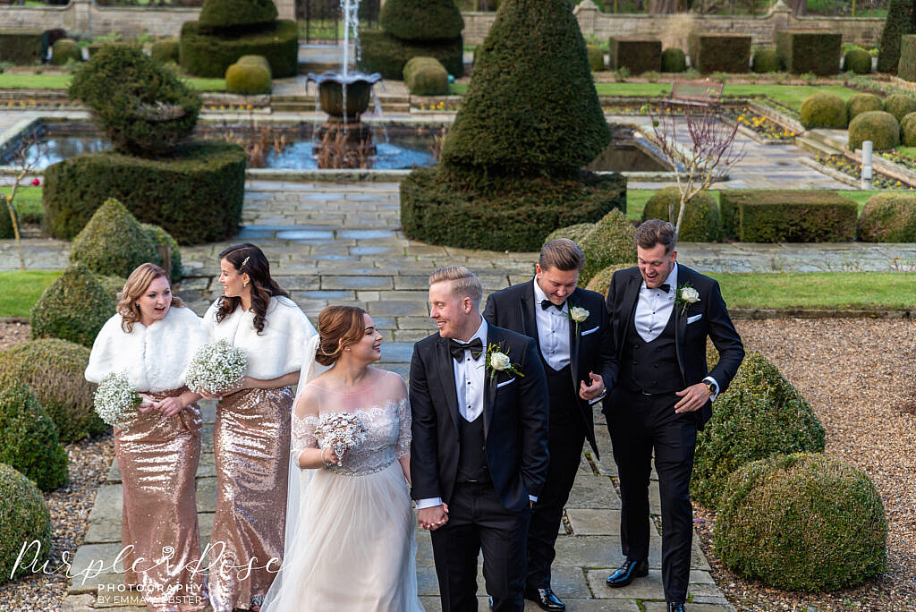 Bride and groom laughing with the wedding party