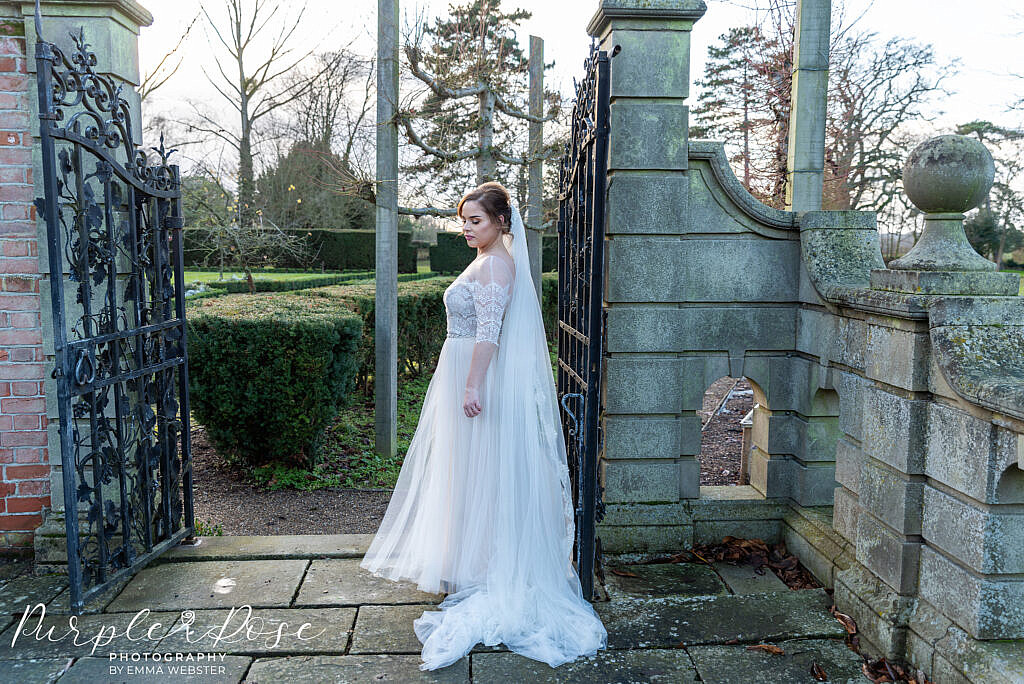 bride waiting by a gate