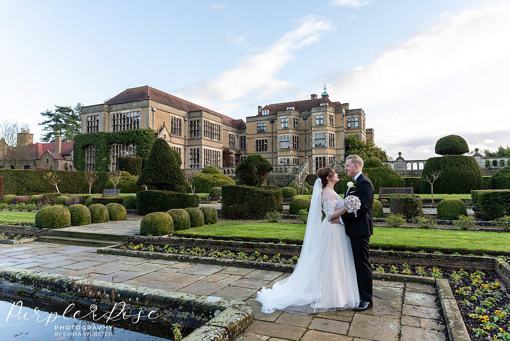 bride and groom stood in front of Farnham Hall