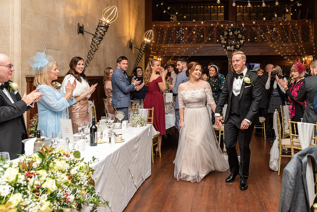 Bride and groom walking into their wedding reception