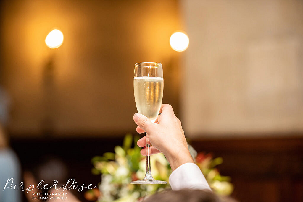 Glass of champagne held aloft