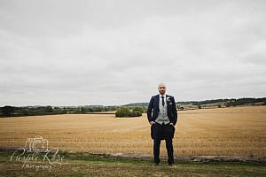 Groom standing in front of open fields