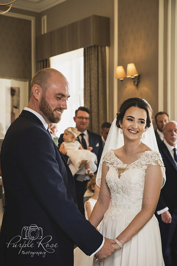 Bride and groom smiling during wedding ceremony