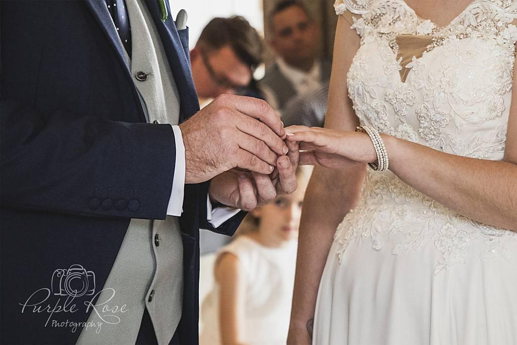 Groom placing wedding ring on brides finger