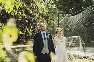 Bride and groom walking round a garden