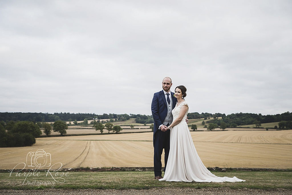 Bride and groom in front of open fields