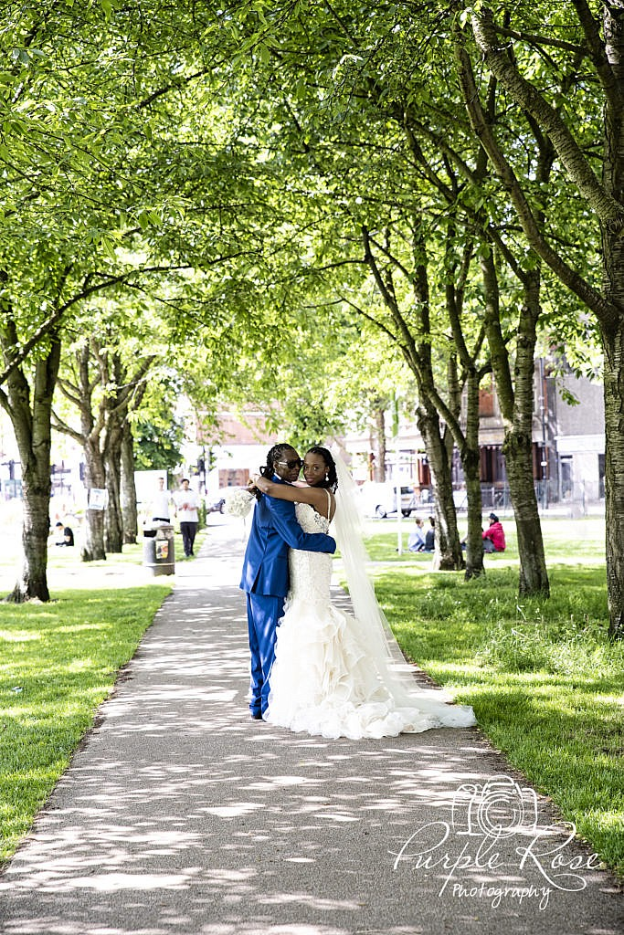Bride and groom embracing in front of a tree lined pathway