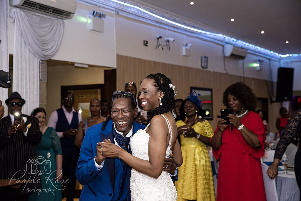 Bride and groom giggling as they dance