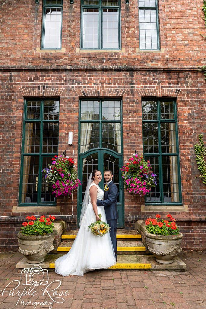 Bride and groom in front of a green door