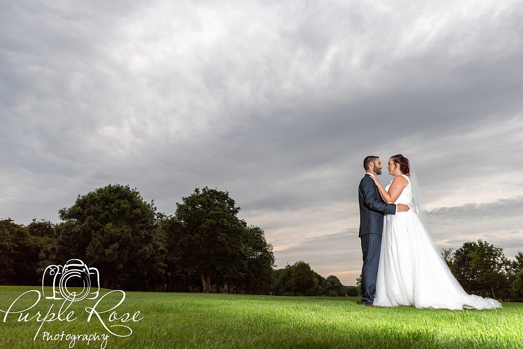 Bride and groom in front of a grey story sky