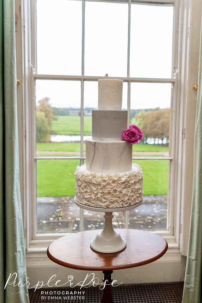 Wedding cake in a window at Kelmarsh Hall Northampton