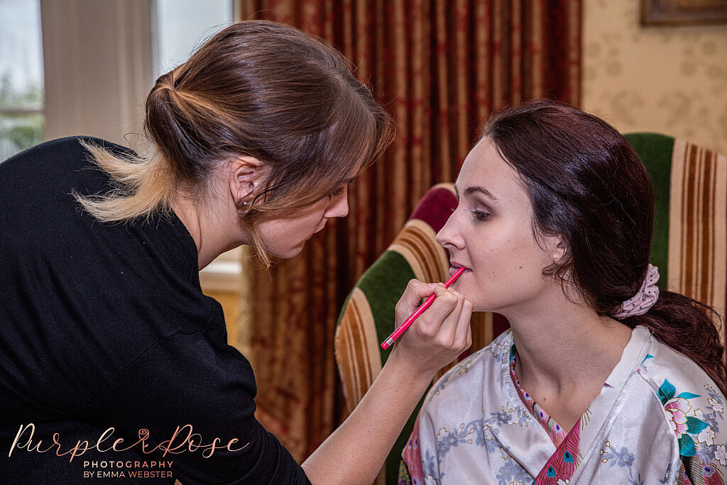 Make up artists applying lip liner