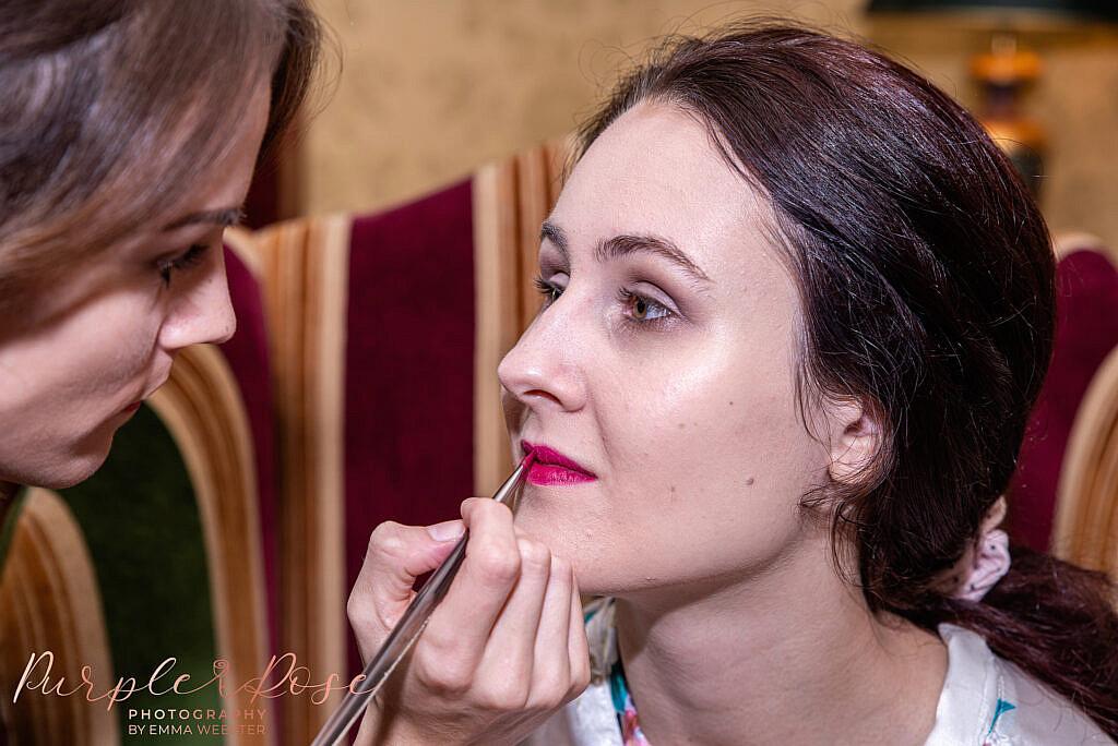 Bridesmaid having lipstick applied