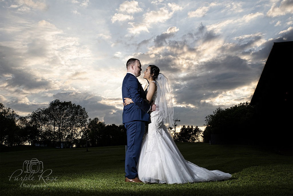 Bride & groom embracing in front of a dramatic sky
